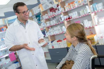 male chemist explaining product-details to customer in pharmacy