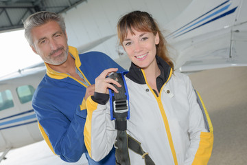 Portrait of man and woman in jumpsuits next to aircraft