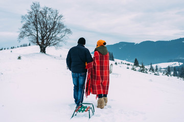 Loving couple walks with sleds in the winter in the mountains.