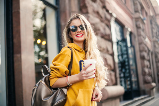 young beautiful blonde drinking coffee walking around the city.mustard sweetshot.,urban backpack , bright red lips Posing against the window of the boutique