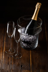 Picture of two glasses, bucket of ice and bottle of wine