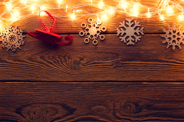 Picture of wooden surface with burning garland on top, snowflakes, red felt toy.