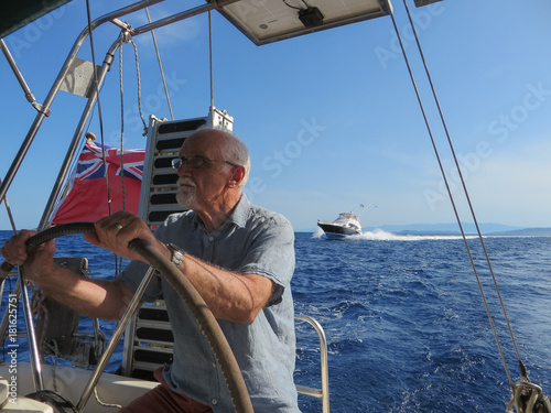Competitions: seventy-year-old man holds a steering wheel of boat