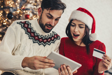 Happy young couple using credit card to shop online. Happy Young man and woman with laptop and credit card buying online. Online christmas shopping.