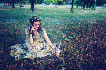 Forest fairy sits on a meadow