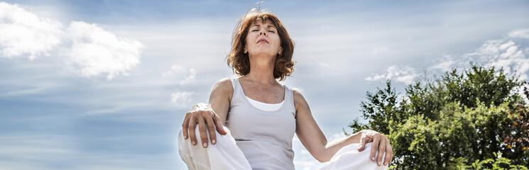 radiant 50s yoga woman seeking for spiritual balance, low angle