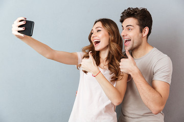 Portrait of a cheerful young couple showing thumbs up