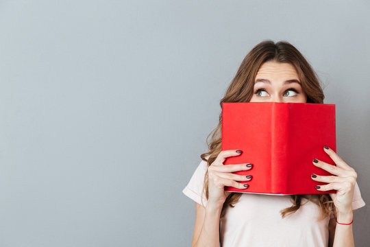 Portrait of a pretty young girl hiding behind an open book