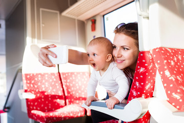 Young mother with smartphone travelling with baby by train.