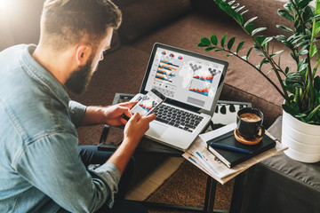 Young man, entrepreneur, freelancer sits at home on couch at coffee table, uses smartphone, on table is laptop with graphs, charts, diagrams on screen.Online marketing,education, e-learning. Startup.