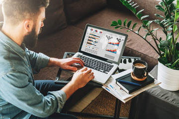 Young bearded hipster man, entrepreneur sits on couch at coffee table,uses laptop with graphs,charts, diagrams on screen.On table notebook,cup of coffee.Online marketing,education,e-learning. Startup.