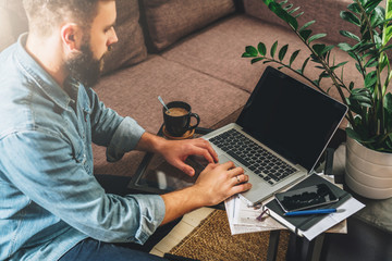 Young bearded hipster man,entrepreneur sits on couch at coffee table,uses laptop with blank screen.On table notebook,cup of coffee, smartphone.Online marketing,education,e-learning.Startup.