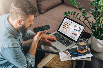 Young bearded hipster man, entrepreneur sits on couch at coffee table,uses laptop with graphs, charts, diagrams on screen and talks on his mobile phone.Online marketing, education,e-learning. Startup.