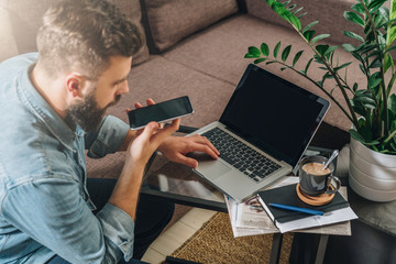 View from above. Young bearded hipster man, dressed in denim shirt, sits at home on couch at coffee table, uses laptop and talks on his mobile phone. Online marketing, education, e-learning. Startup.
