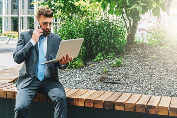 Summer day. Young bearded businessman in suit and tie sitting in park on bench, holding laptop and talking on cell phone. Man is working, studying online. Online marketing, education, e-learning.