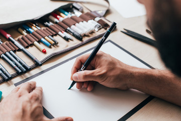 Painter, graphic designer or calligraphy artist sits at table with different kinds of tools, brushes, marker and pen, opens his pencil or brush with black ink. concept artisan hipster work