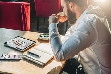View in profile. Young businessman is sitting at table,drinking coffee.On table is tablet computer,smartphone with graphs, charts, diagrams on screen, notebook. Man working, learning.Online marketing.