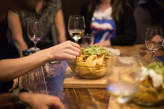 Group of friends hang out at downtown local cafe or bar at night, share party snack, bowl of mexican corn nachos topped with fresh guacamole. Partygoers eat tapas and drink wine