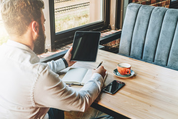 Back view.Young bearded businessman in white shirt is sitting at table,using tablet computer and making notes in notebook.On table is smartphone and cup of coffee.Online marketing,education,e-learning