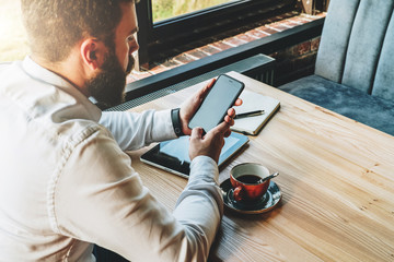 Back view.Young bearded businessman in white shirt is sitting at table,using smartphone, looking on his screen.On table is tablet computer,cup of coffee, notebook.Online marketing,education,e-learning