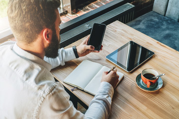 Back view.Young bearded businessman in white shirt is sitting at table,using smartphone and making notes in notebook.On table is tablet computer and cup of coffee.Online marketing,education,e-learning