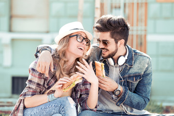 Couple eating sandwich and talking outdoor.