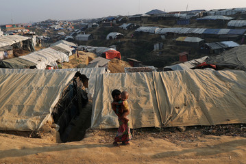 A Rohingya refugee girl carries a child in the Kutupalong refugee camp near Cox's Bazar