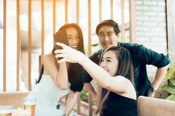 Group of asian smiling friends taking funny selfie in restaurant.