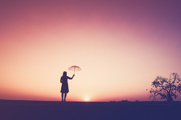 The silhouette of the lonely young woman  holding an umbrella on the cliff at the sunset