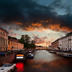 Canal with Moyka river in Saint-Petersburg with dramatic cloudy sky. View from Nevsky Prospect.