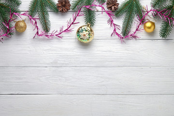 Christmas background. Branches of a Christmas tree, pine cones and balls on a white wooden background.