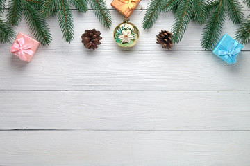 Christmas background. Branches of a Christmas tree, pine cones, ball and gift boxes on a white wooden background.