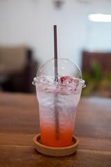 Closeup of strawberry soda in plastic glass