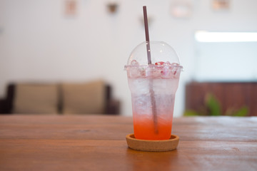 Strawberry soda in plastic glass on wood table