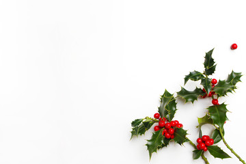Christmas holly floral decoration on white background. Evergreen leaves with red berries and empty space for holiday text. Styled stock photo, top view.