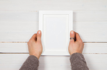 Woman's holding a blank picture frame over a wooden background