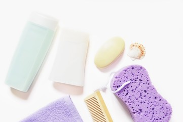 Flat lay organic bath products/ Shampoo, shower gel, terry towel, baby soap, wooden hair brush and purple sponge