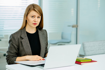 Successful professional woman sitting at office table, looking at camera working with document at laptop computer screen.