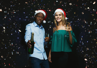 Joyful couple congratulating on christmas with champagne at black background