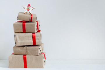 A pile of Christmas gifts in colorful wrapping with ribbons and star on top against the wall on a white wooden floor with copyspace.