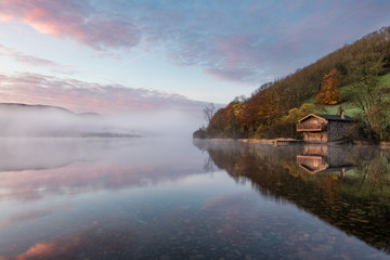 Boathouse at Ullswater Lake with beautiful dawn sunrise colour in the sky, lake mist and calm reflections.