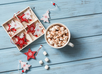 Hot chocolate with marshmallows and cinnamon, christmas decorations on a blue wooden background. Christmas background. Free space, top view, flat lay