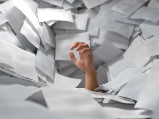 hand drowning in paper sheets