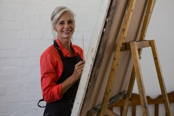 Portrait of smiling senior artist painting while standing by