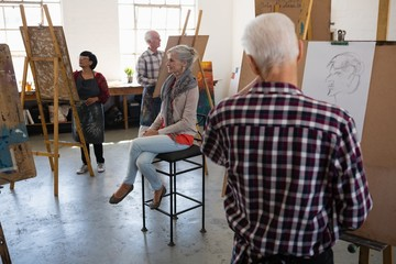 Senior woman sitting on chair while artists sketching on paper