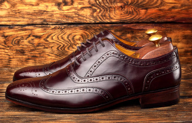 Brown man's shoes brogues on wooden background