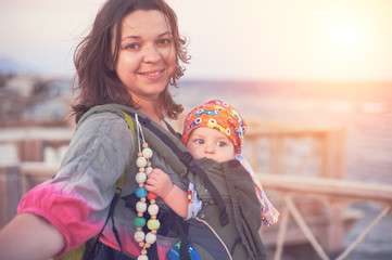 A young mother is on the beach with her baby in a sling