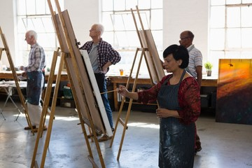 Senior male and female artists painting on easel