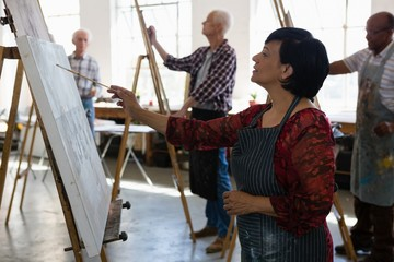 Senior female and male artists painting on easel