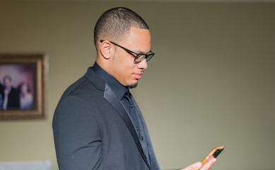 young black man with phone in hand reading